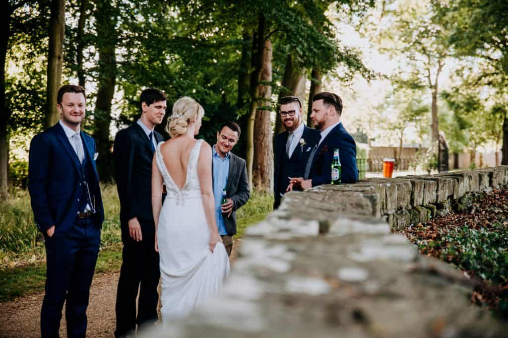 A bride and groom chat with their wedding guests outside in their wedding venue gardens