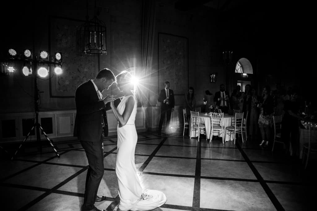 A black and white image showing a bride and groom enjoying their first dance with wedding guests watching on in the background