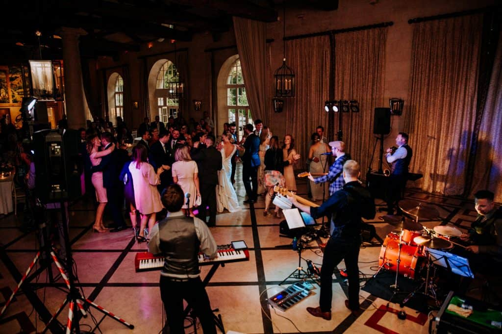 A colour image depicting a busy dance floor as a live band plays on in the foreground of the photograph