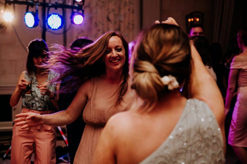 Two female wedding guests enjoy dancing together at a wedding