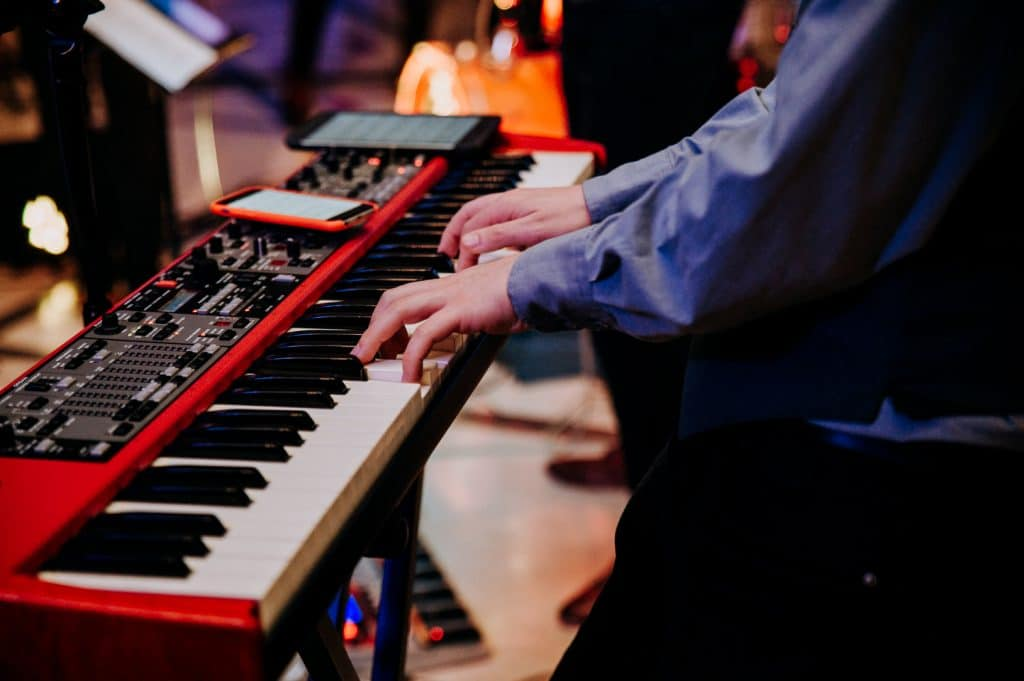 A close up of a musical keyboard being played at a wedding