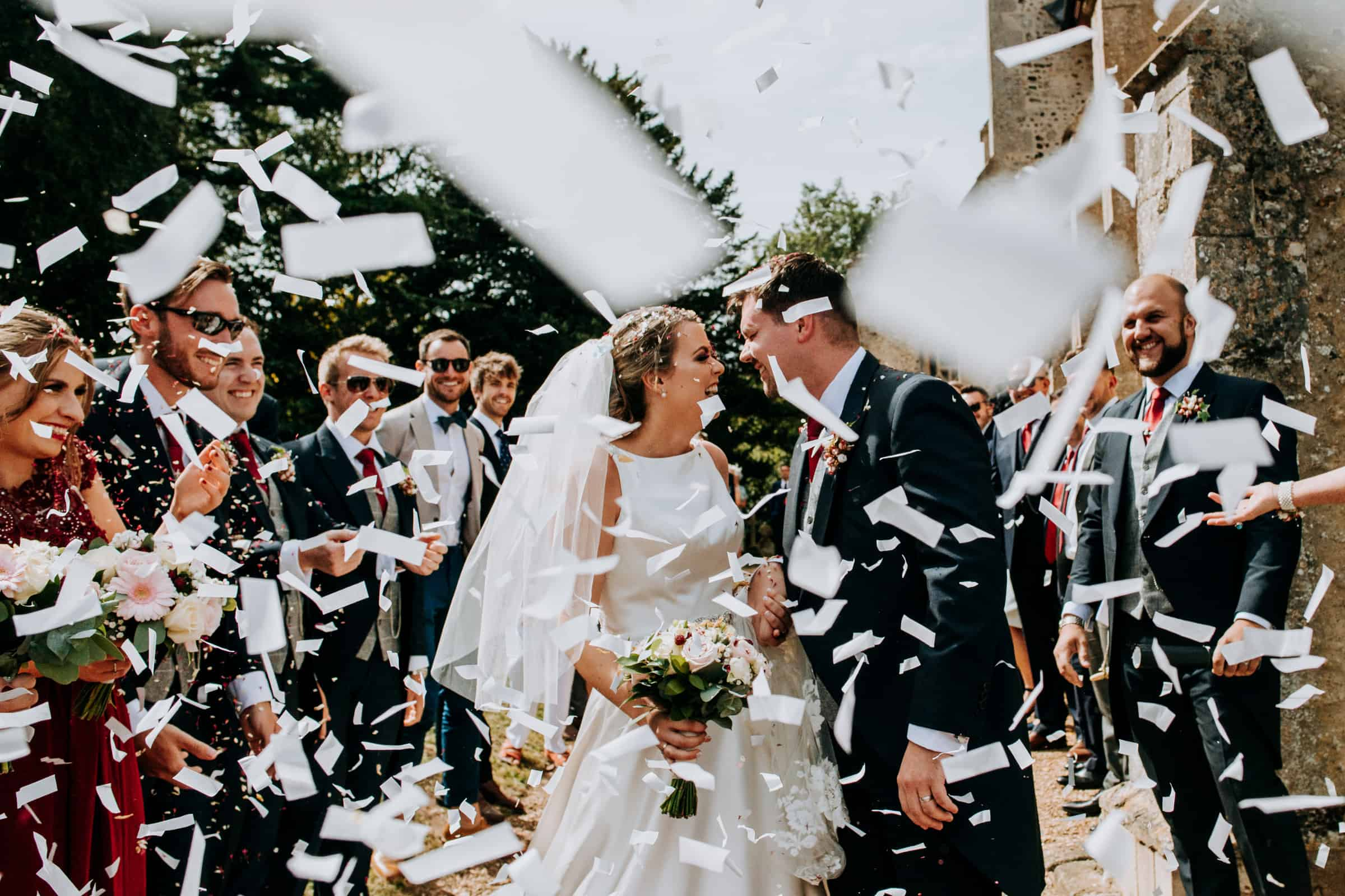 A bride and groom are showered with confetti on their wedding day
