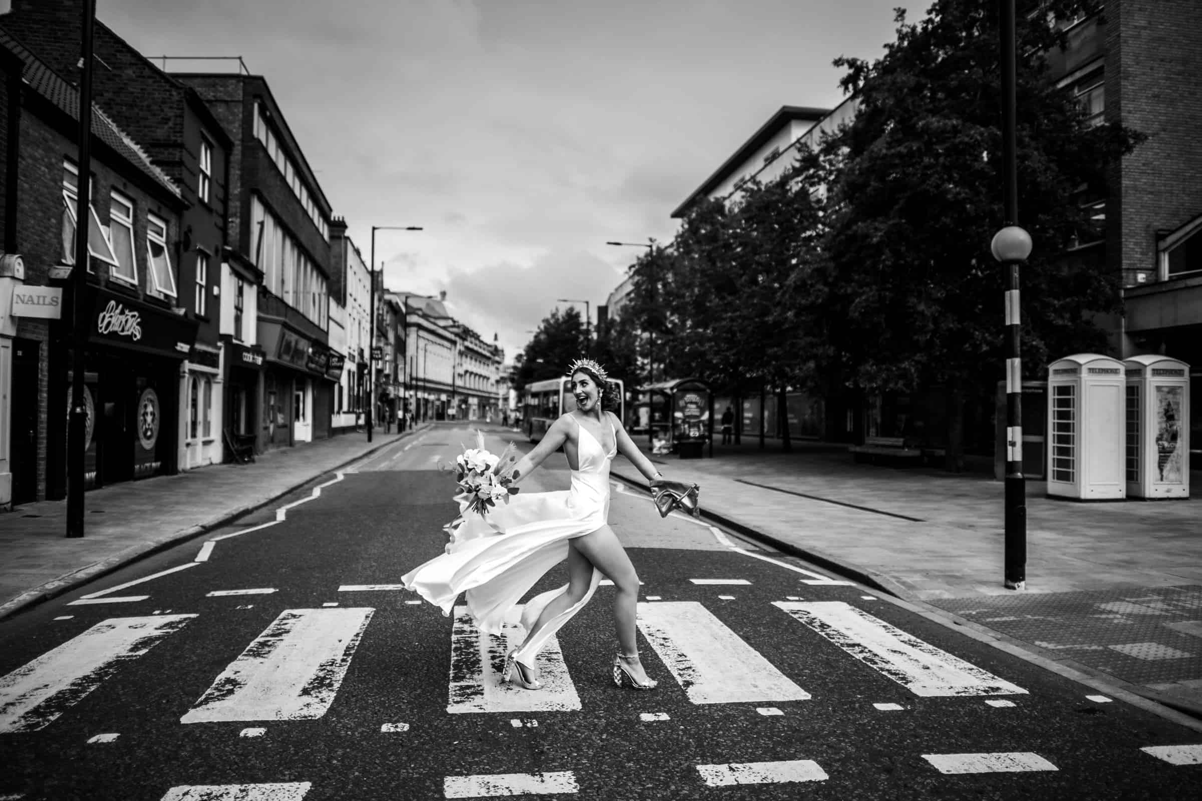 A Yorkshire bride walks confidently across the road in the city of Hull captured by award winning Yorkshire wedding photographer M and G Wedding Photography
