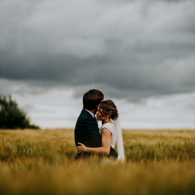 Bride and groom share a hug in a field with a cloudy sky overhead