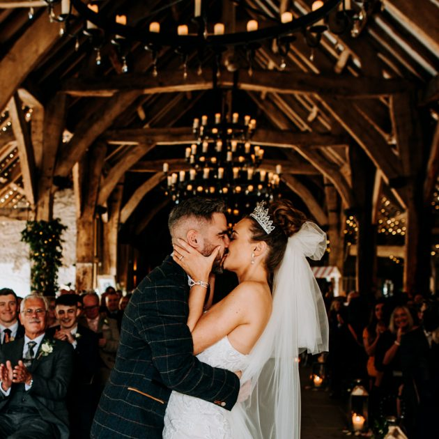 A bride and groom kiss during their barn wedding ceremony