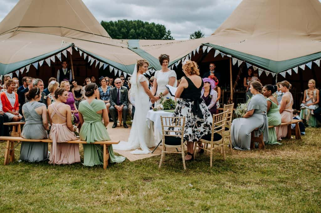 Wedding guests and two brides enjoy this outdoor wedding at Hitchin Lavender