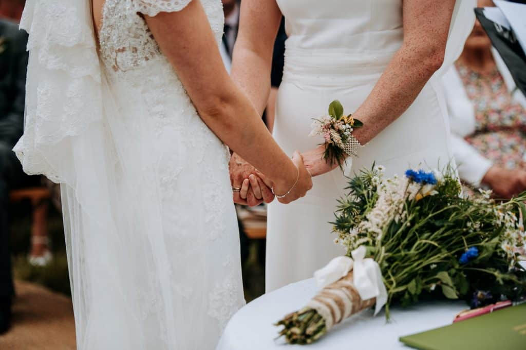 Two brides hands tenderly during their wedding ceremony