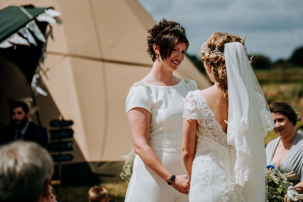 A female same sex couple hold hands during the outdoor wedding ceremony