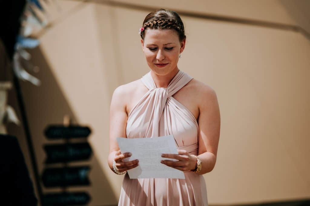 A bridesmaid reads a poem at an outdoor wedding