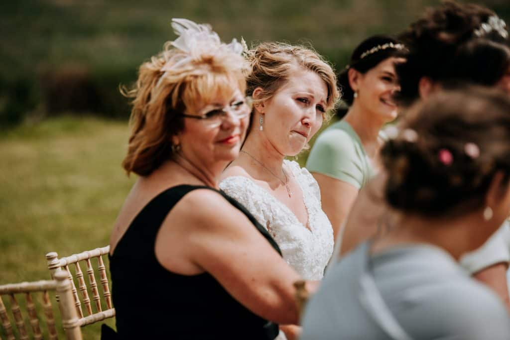 A bride gets very emotional surrounded by her guests during her wedding ceremony