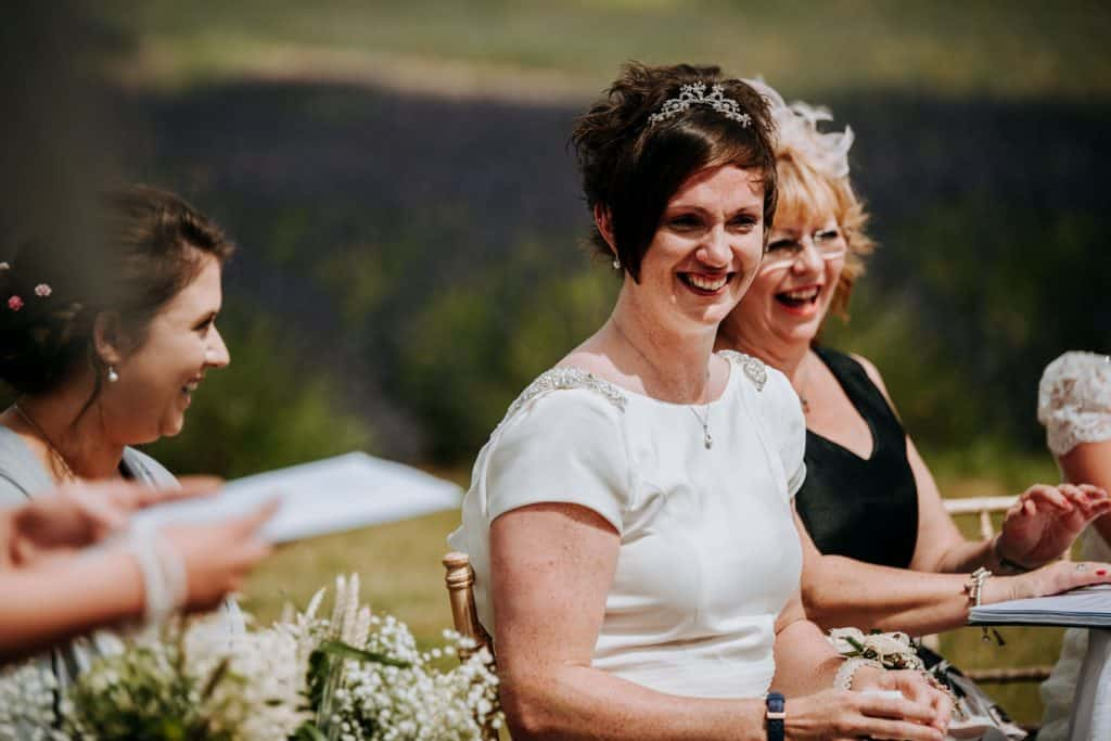 A bride laughs during her outdoor wedding
