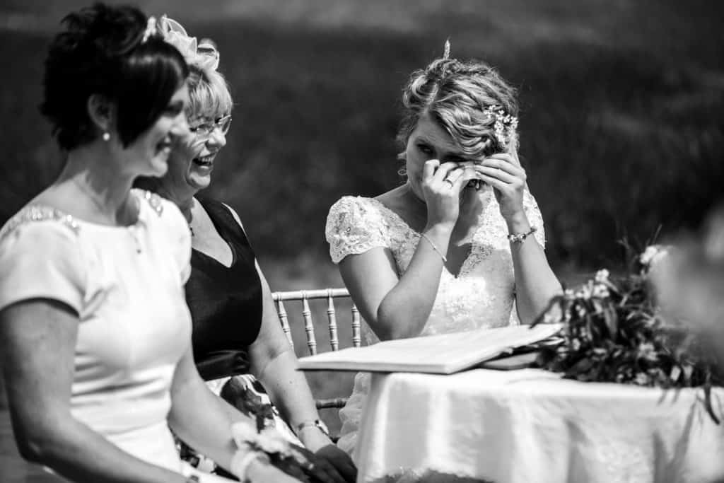An emotional bride is shown crying captured by M and G Wedding Photography