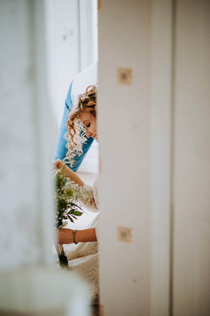 A bride adjusts her floral bouquet