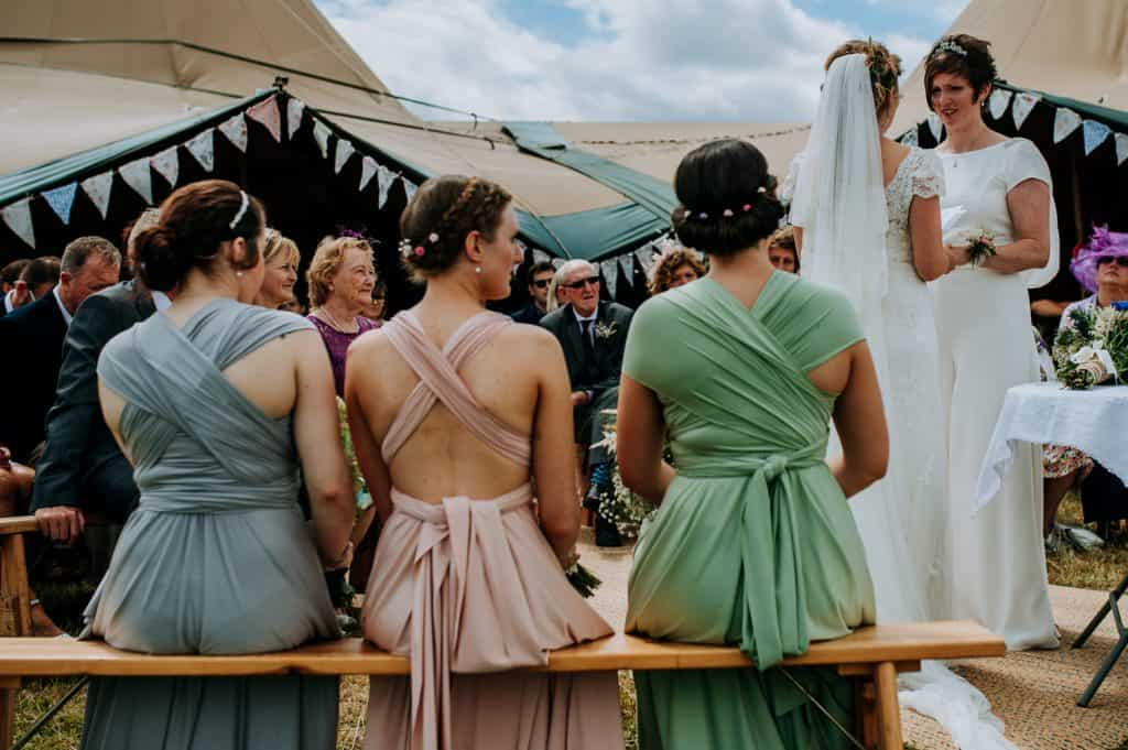 Three bridesmaids wearing different coloured dresses sit together during an outdoor ceremony