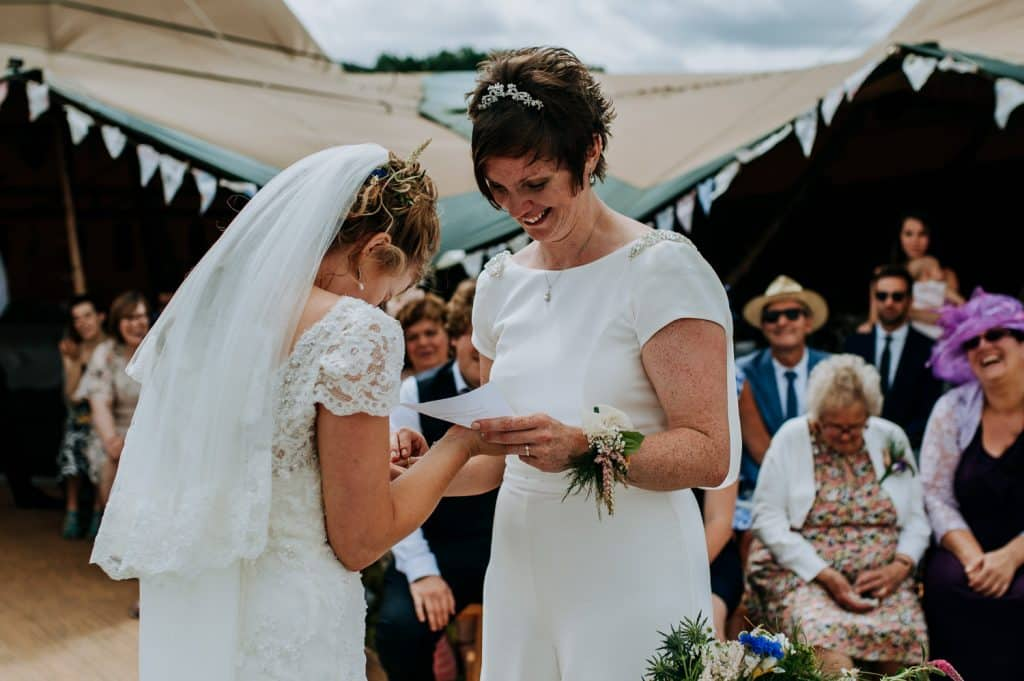 Two brides laugh together on their wedding day