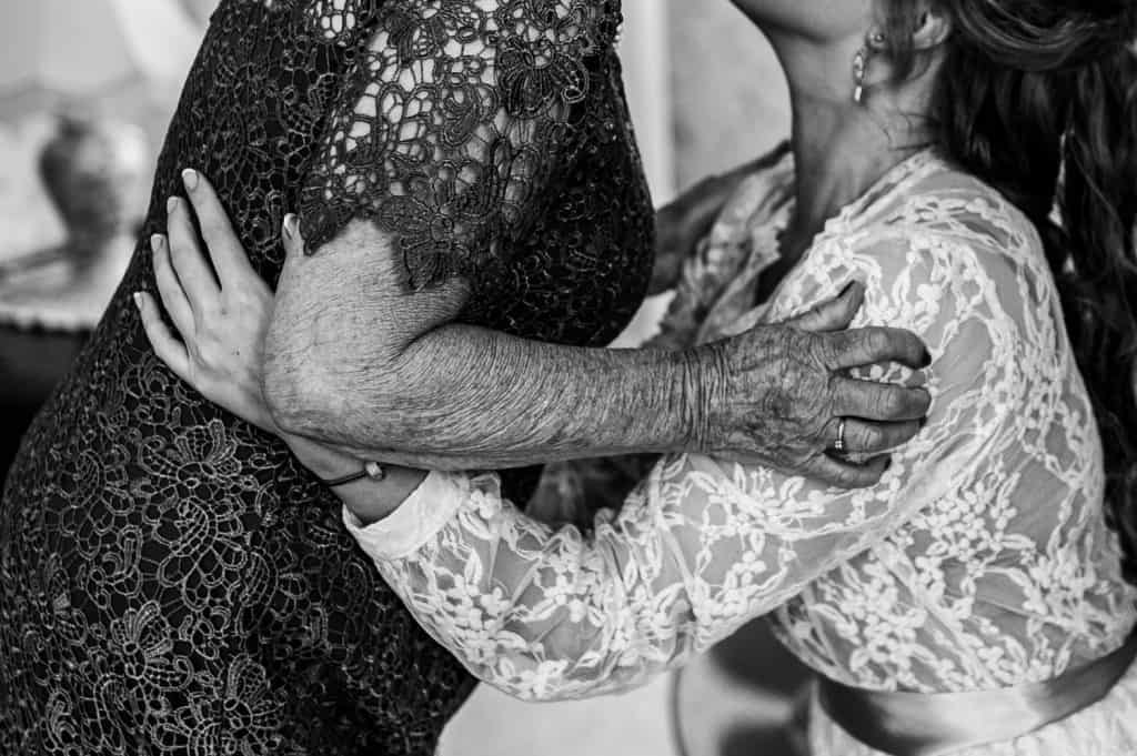 A bride and her elderly grandmother embrace
