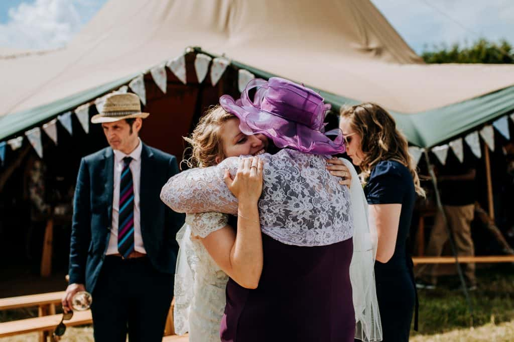 A bride hugs one of her wedding guests