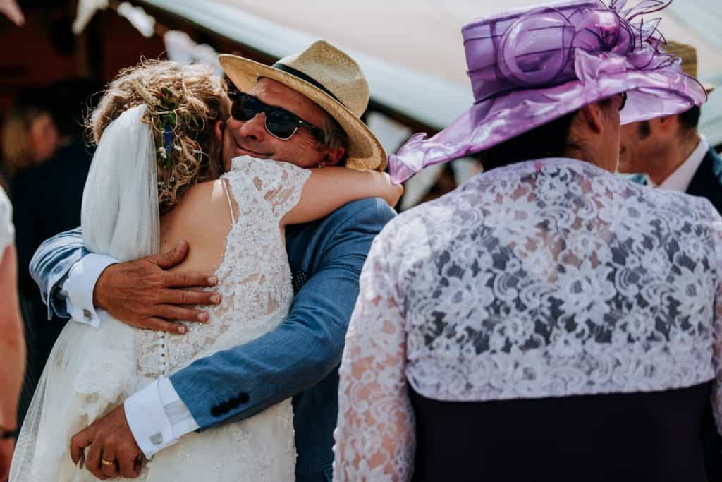 A bride and a wedding guest share a hug