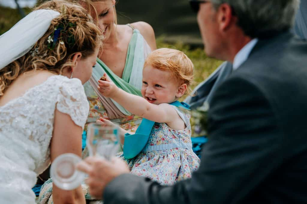 A young wedding guest and her family have fun with one of the brides at this same sex wedding