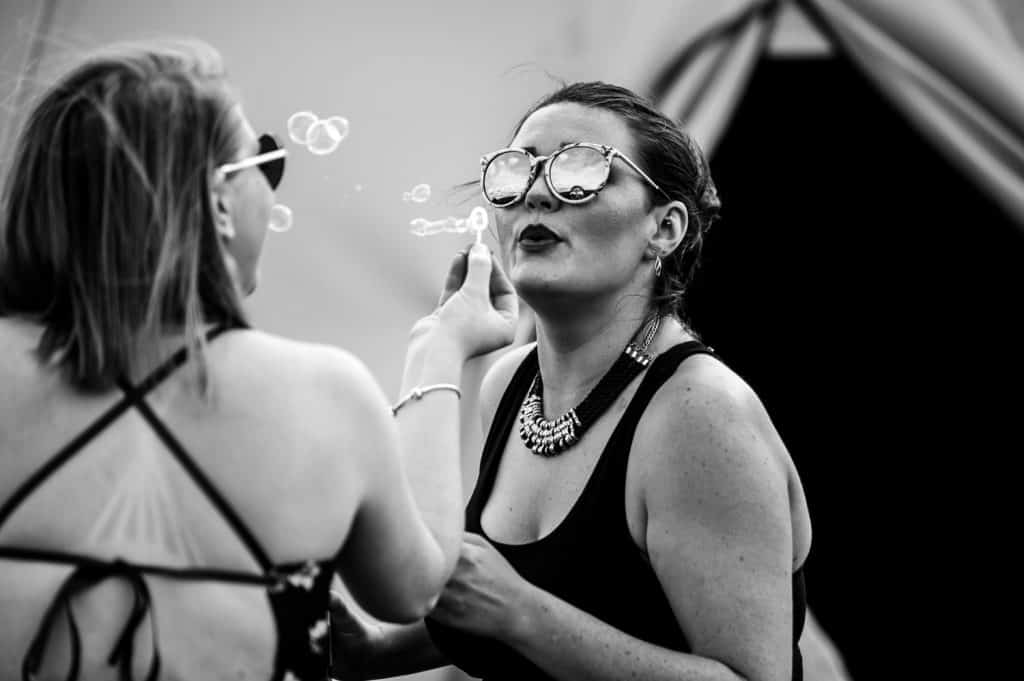 A black and white photo of the two adult female wedding guests playing with bubbles