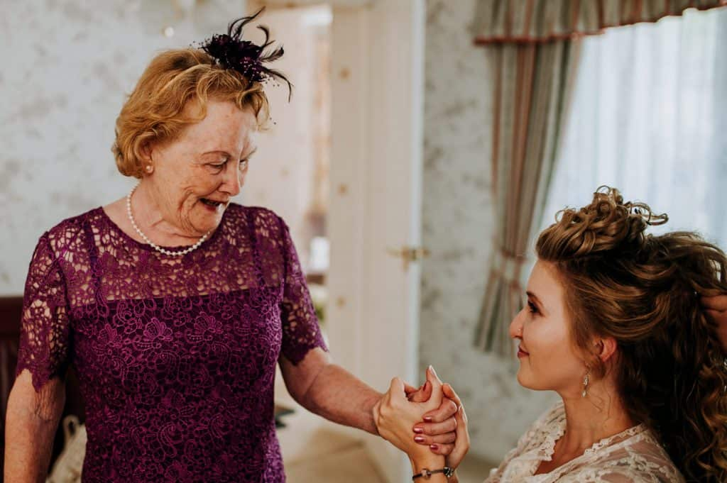 A touching moment on a wedding morning as a bride holds her grandmother's hand