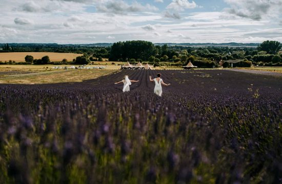 Two brides run through the purple fields at Hitchin Lavender wedding venue