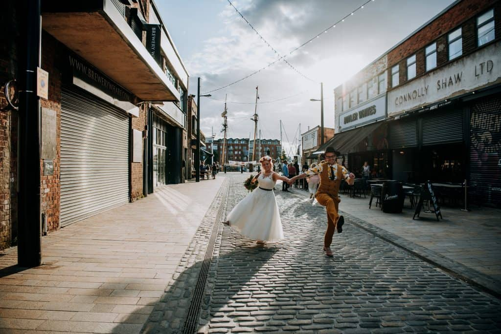 A bride and groom skip happily through the streets of Hull just after being married