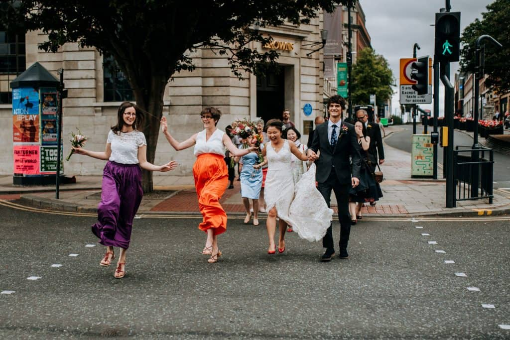 A bride, groom and their wedding guests crossing the road in Leeds