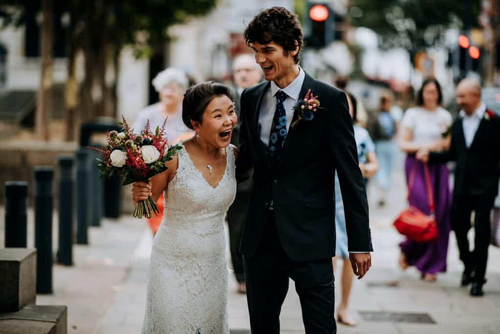 a bride and groom walk excitedly together before their ceremony
