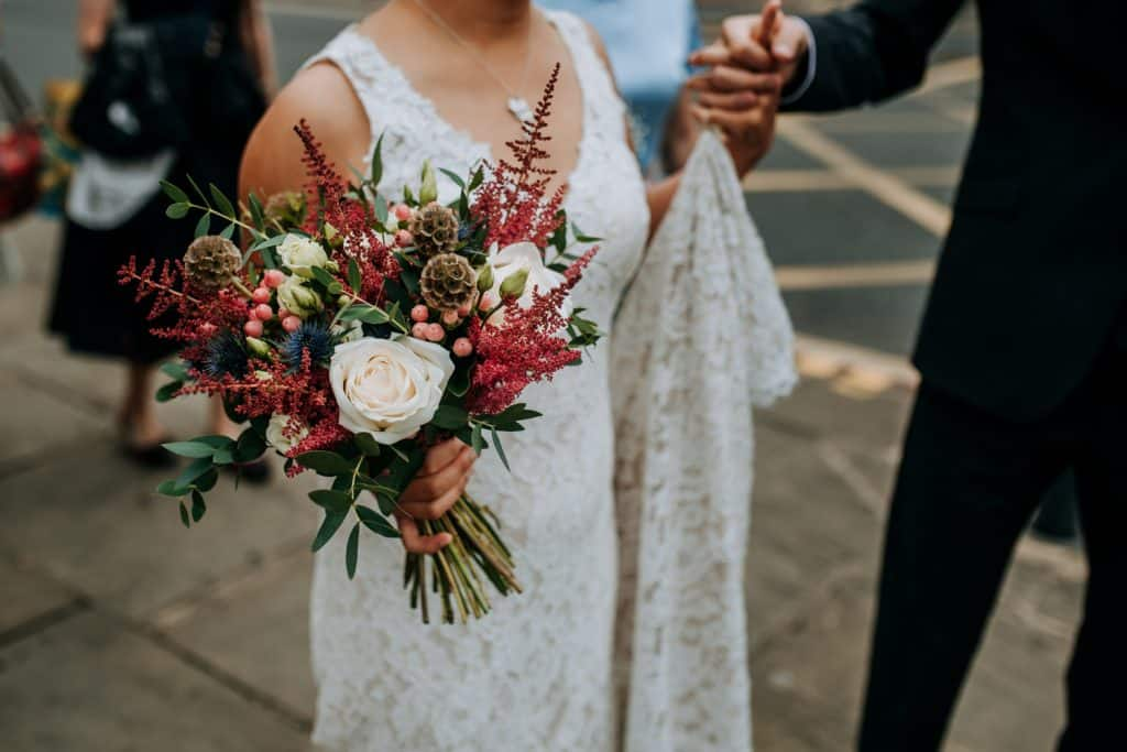 A bride holds her beautiful bridal bouquet of avalanche roses, berries and red astilbe