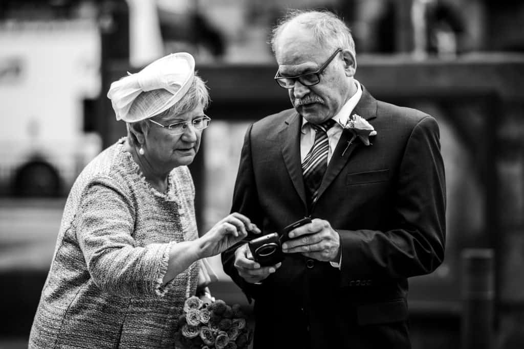 elderly woman shows husband how to take photo on his camera phone