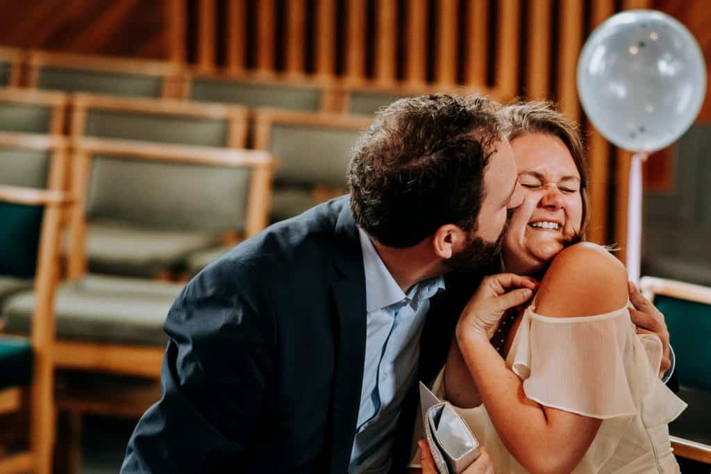a man kisses his excited wife on the cheek