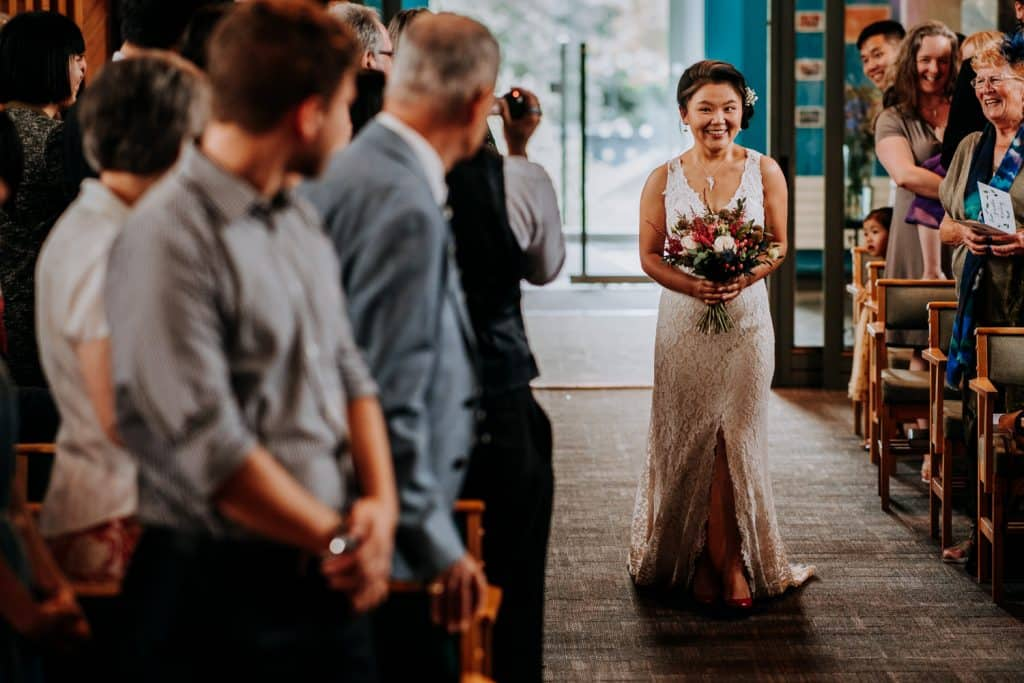 without following tradition the bride walks down the aisle alone, with a big smile on her face