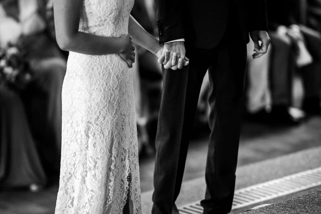 a close black and white image of the couple hold hands