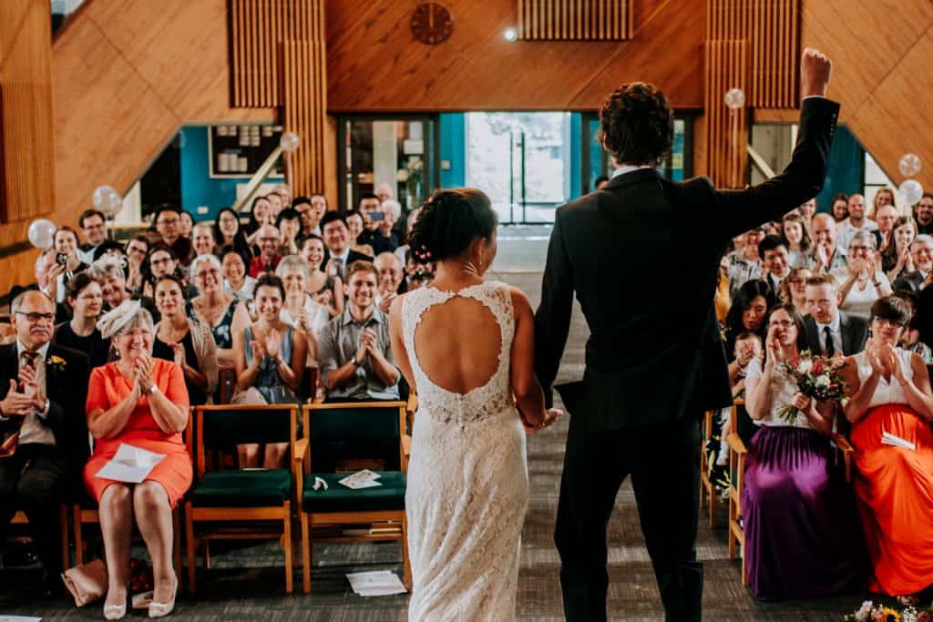 guests clap while the groom excitedly throws fist into the air