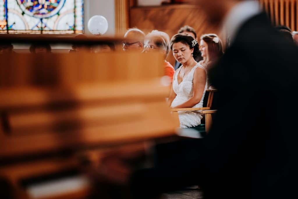 bride tentatively listens with eyes closed
