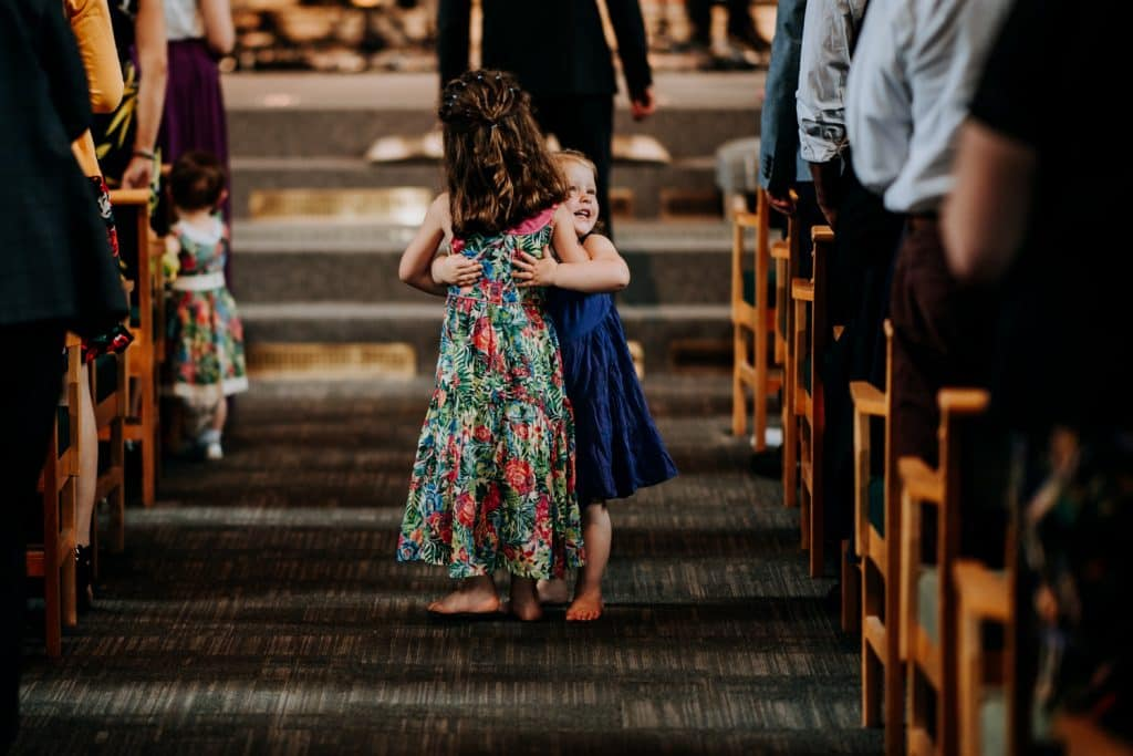 two children share a hug after the ceremony