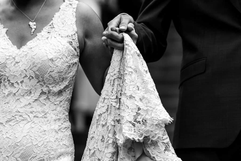 black and white photo of husband and wife holding hands and the dress train.