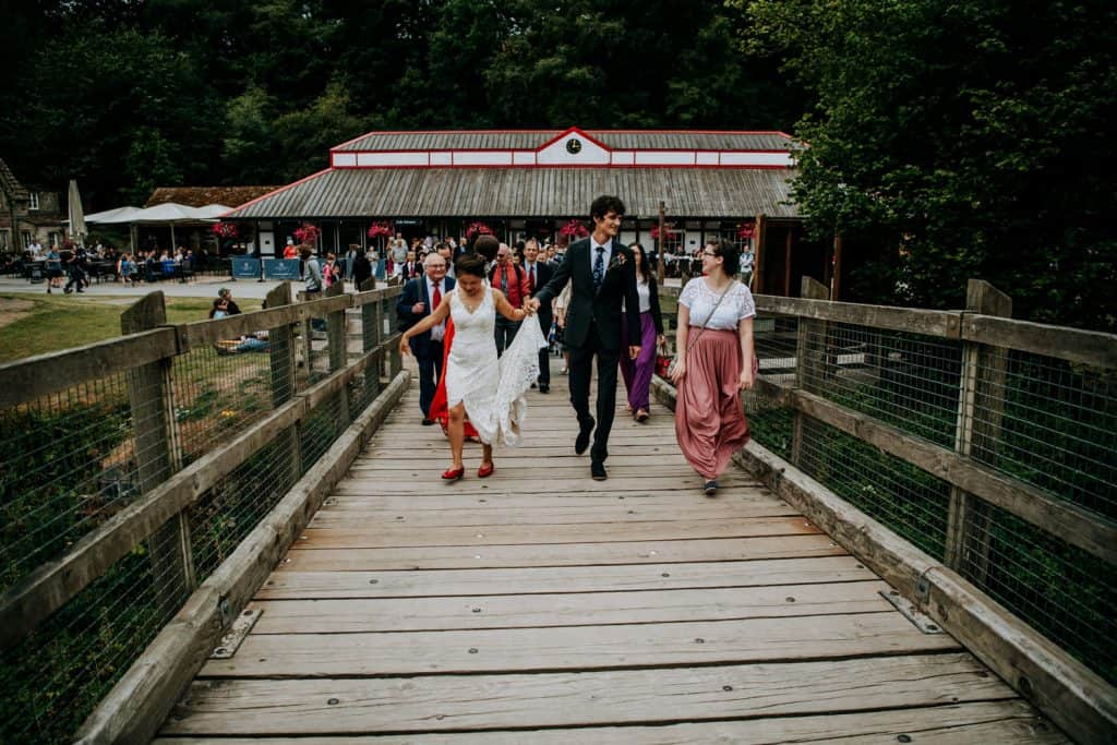 husband and wife lead as guests cross a bridge