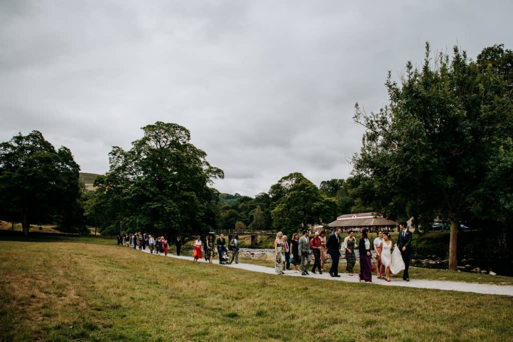 white shot of all wedding guests walking