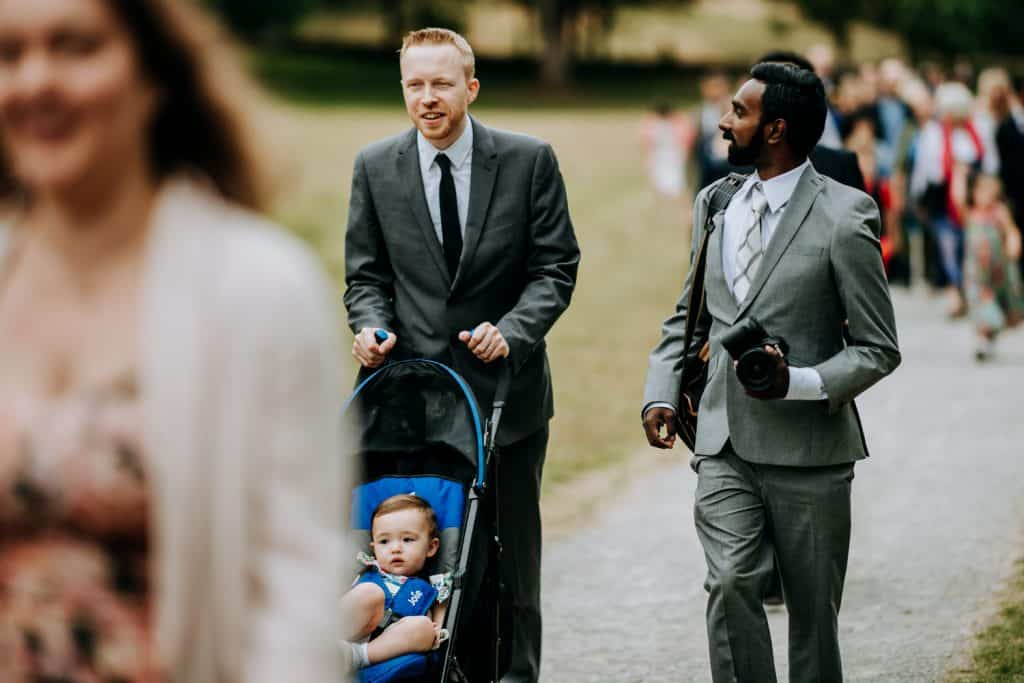 wedding guests walking with baby in pushchair