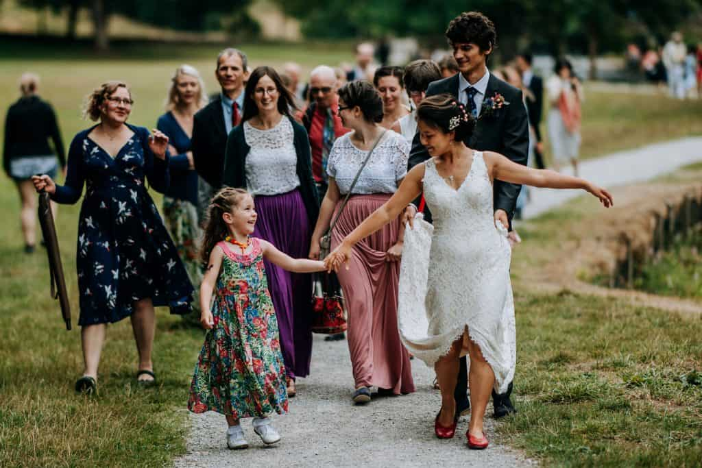 a beautiful moment captured of bride holding hands with young girl