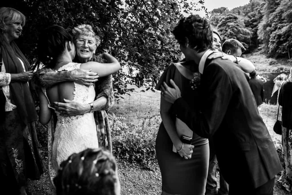 bride and groom kissing and hugging relatives