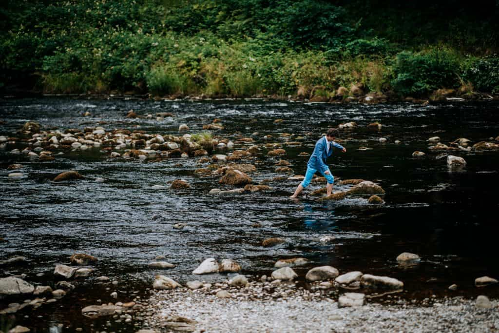 groomsman in blue trousers stepping stones in stream