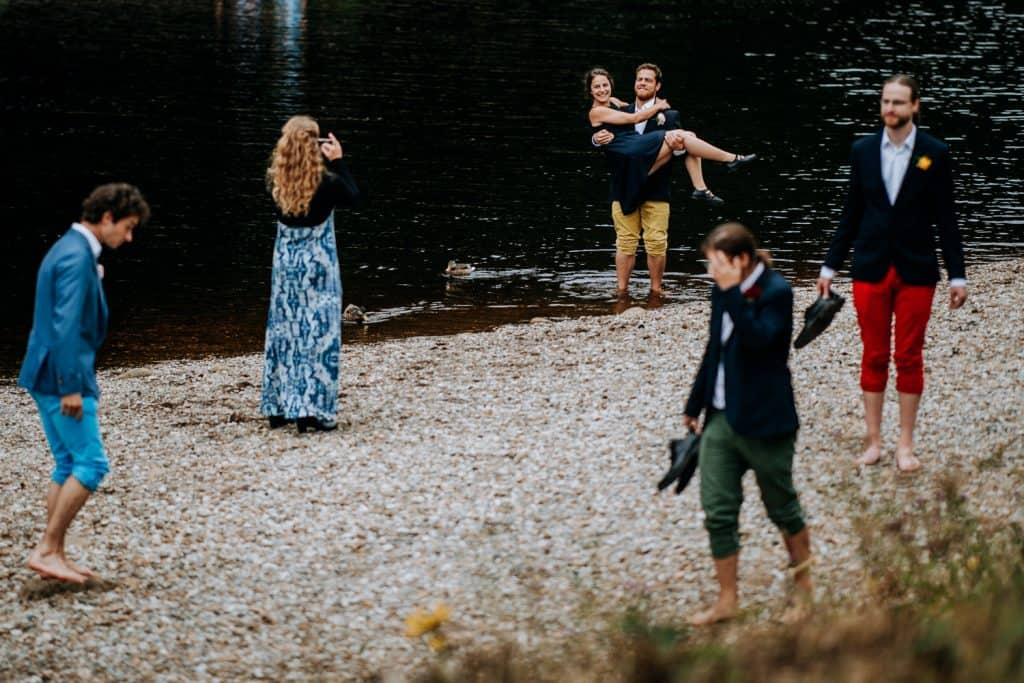 wide shot of guests groomsman also carries a woman in the water