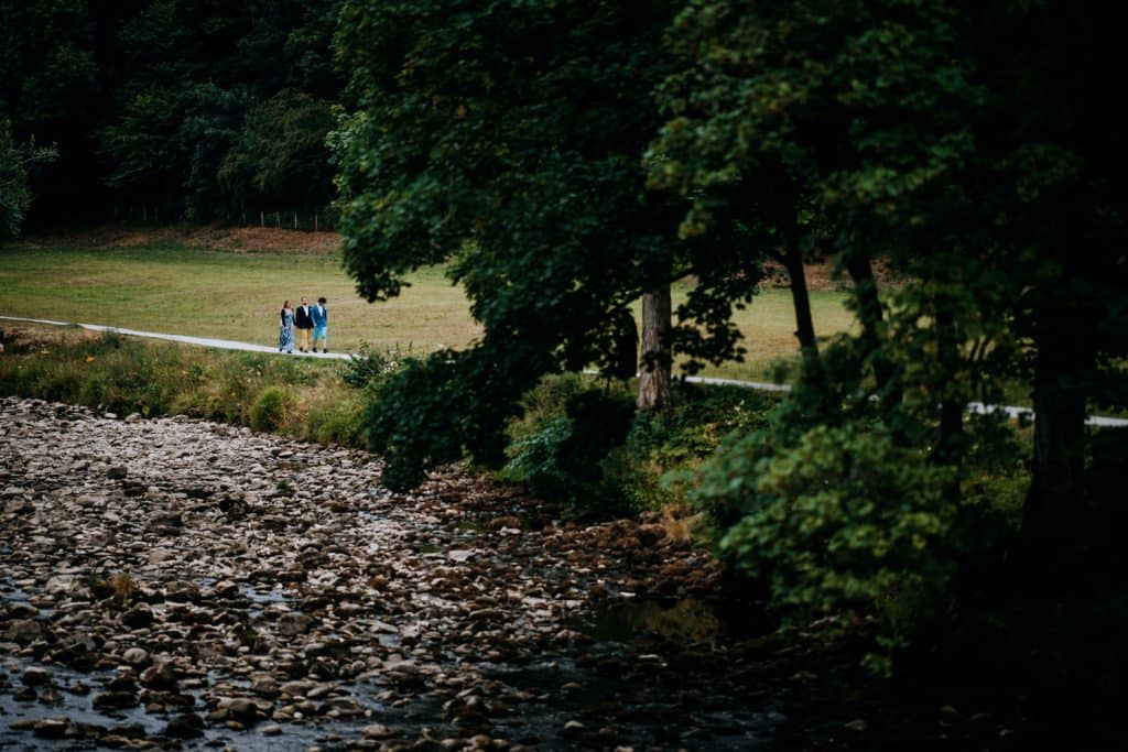 wide shot of the last few guests walking through trees at Bolton Abbey