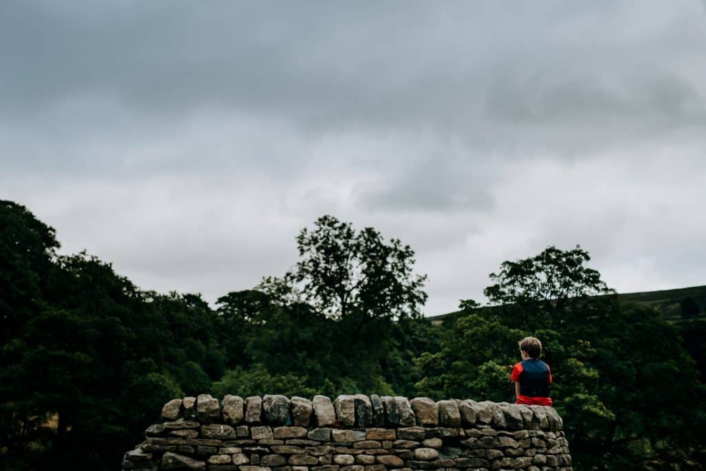 boy in red sits alone on a stone wall, the sky is grey