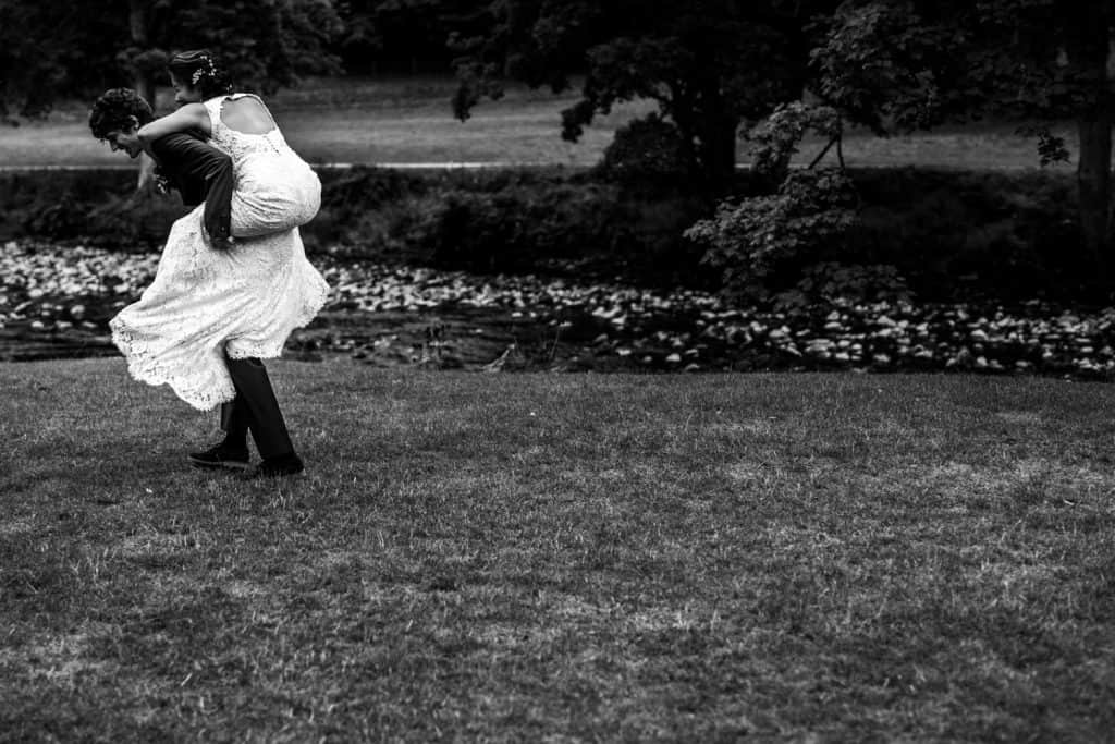 groom gives his bride a piggyback