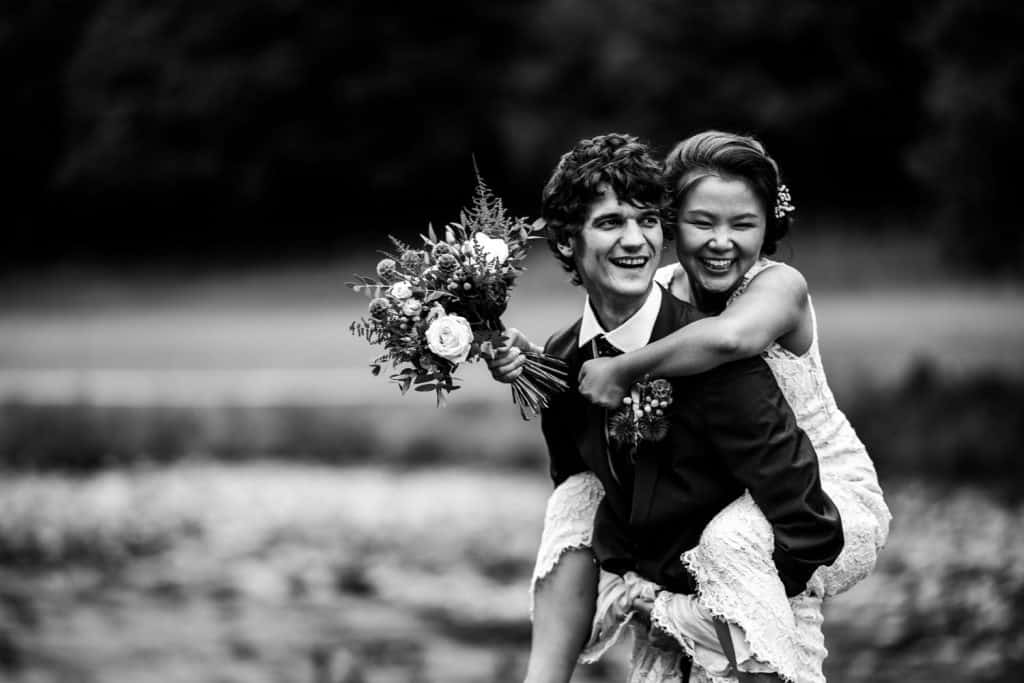 close up black and white image of bride on grooms back, looking happy