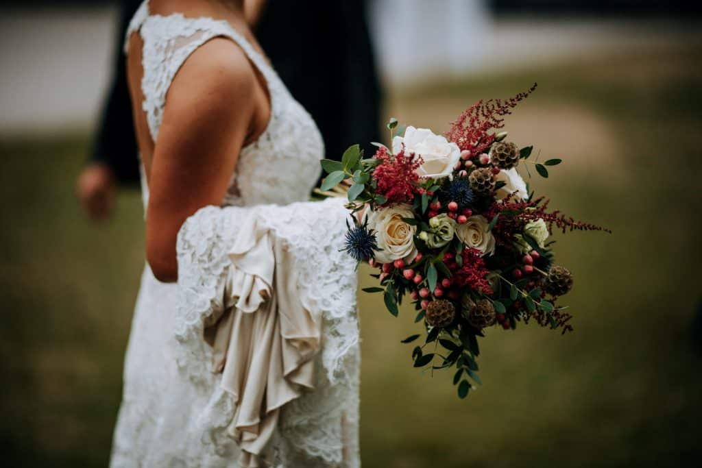 a brides dress is draped over her arm as she carries her flowers